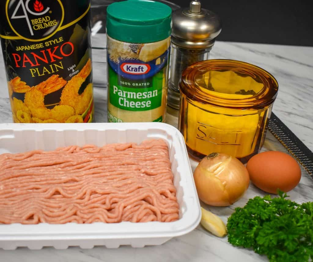 The ingredients for chicken meatballs displayed on a white table.