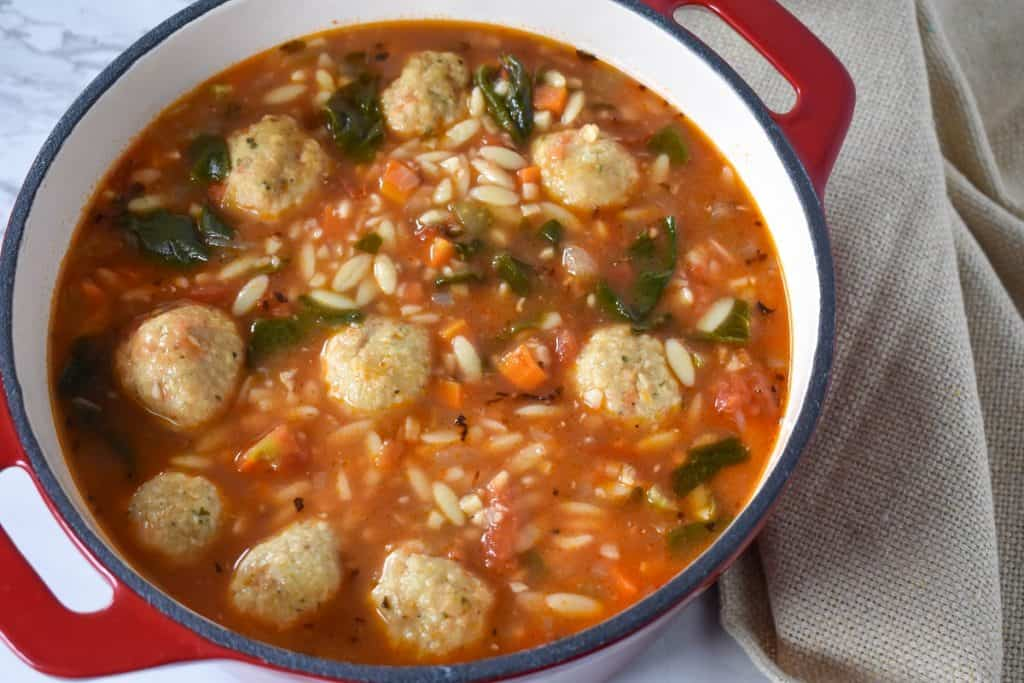 Chicken meatball soup in a red dutch oven.