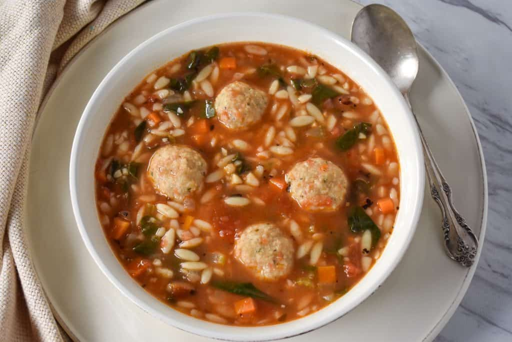 Chicken meatball soup served in a large white bowl.
