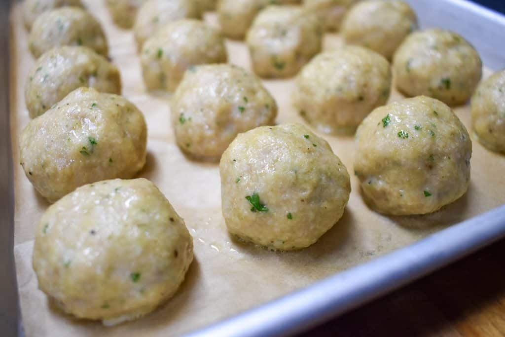 Cooked chicken meatballs arranged on a baking sheet lined with parchment paper.