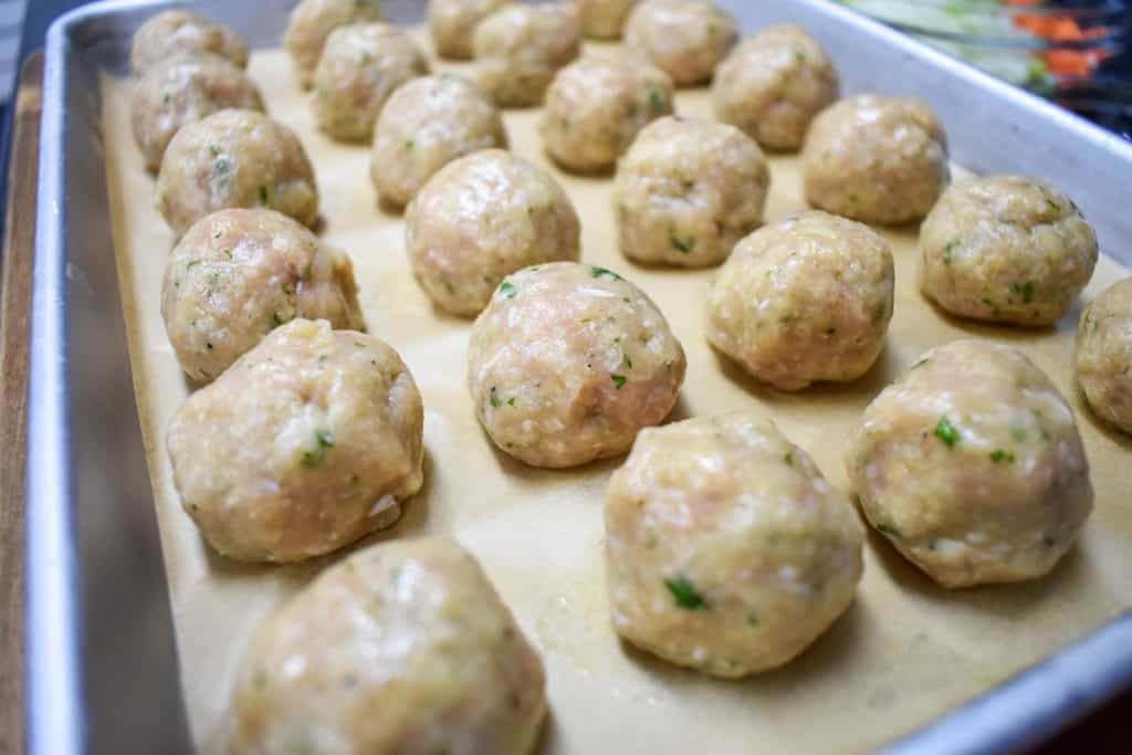 Small chicken meatballs before cooking, arranged on a baking sheet lined with parchment paper.