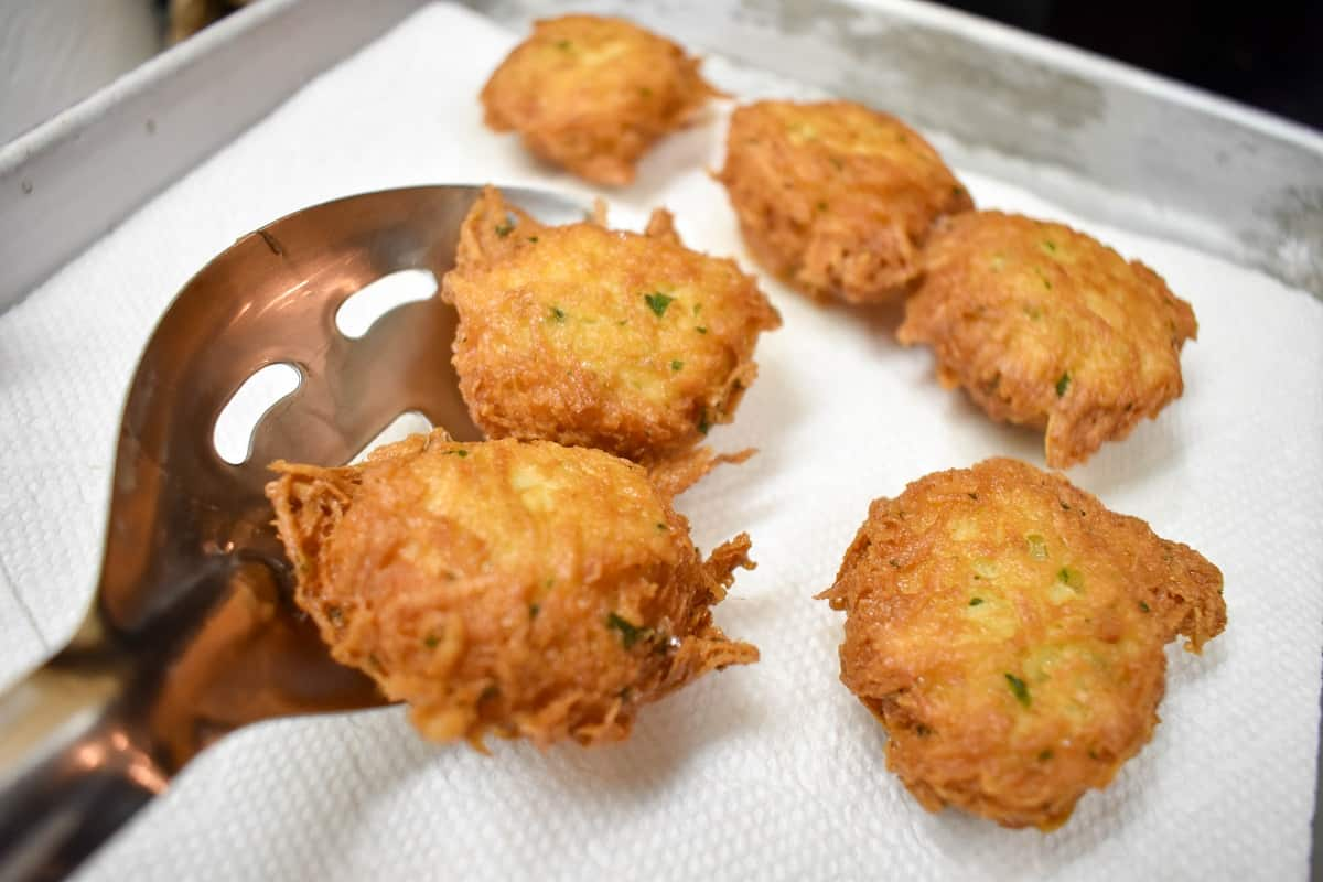 Malanga fritters being placed by a slotted spoon on a paper towel lined pan to drain.