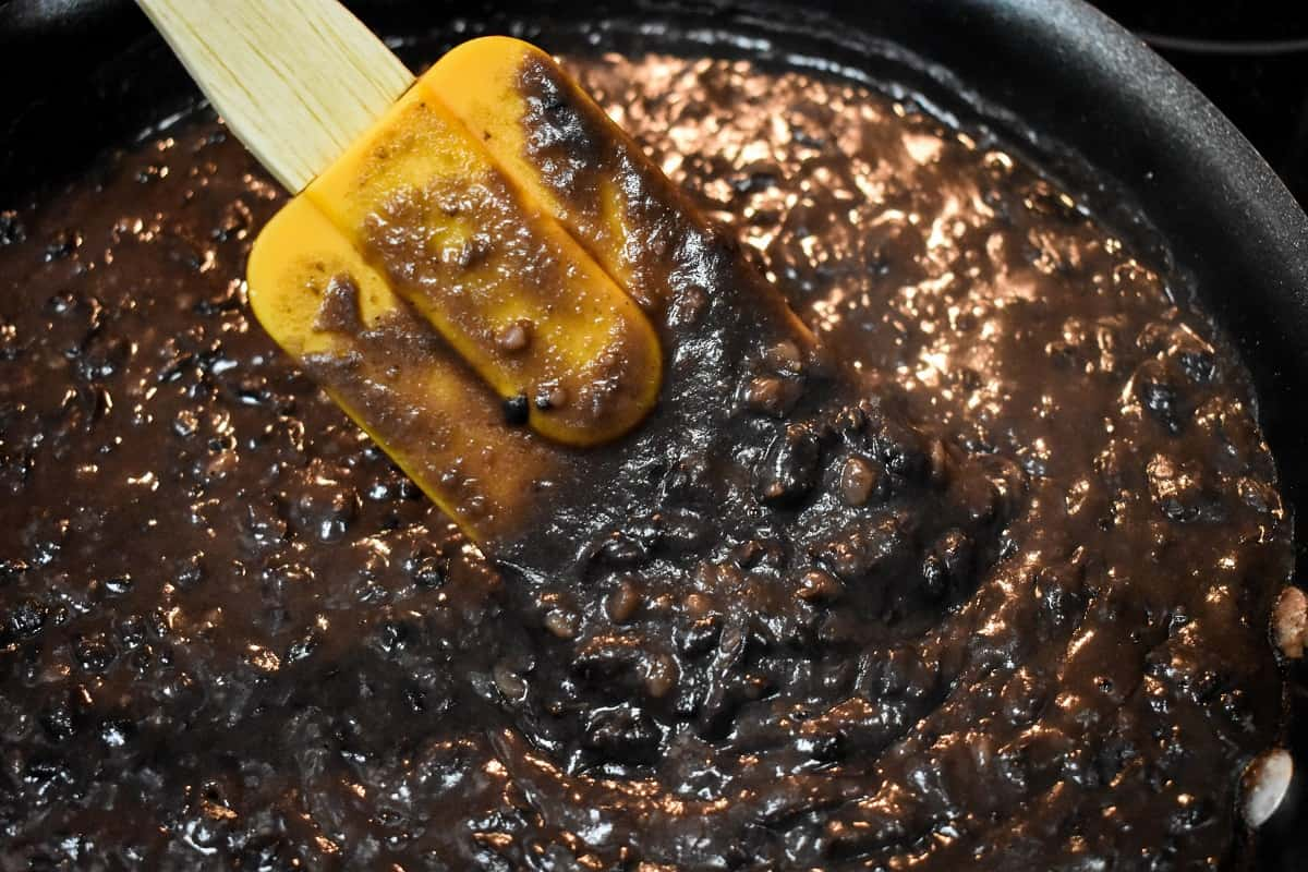 Black beans being mashed in a black non-stick skillet with an orange rubber spatula.