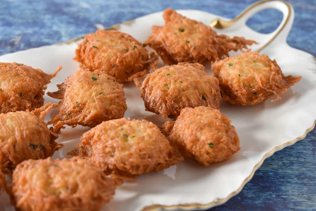 Malanga fritters displayed on a white platter.
