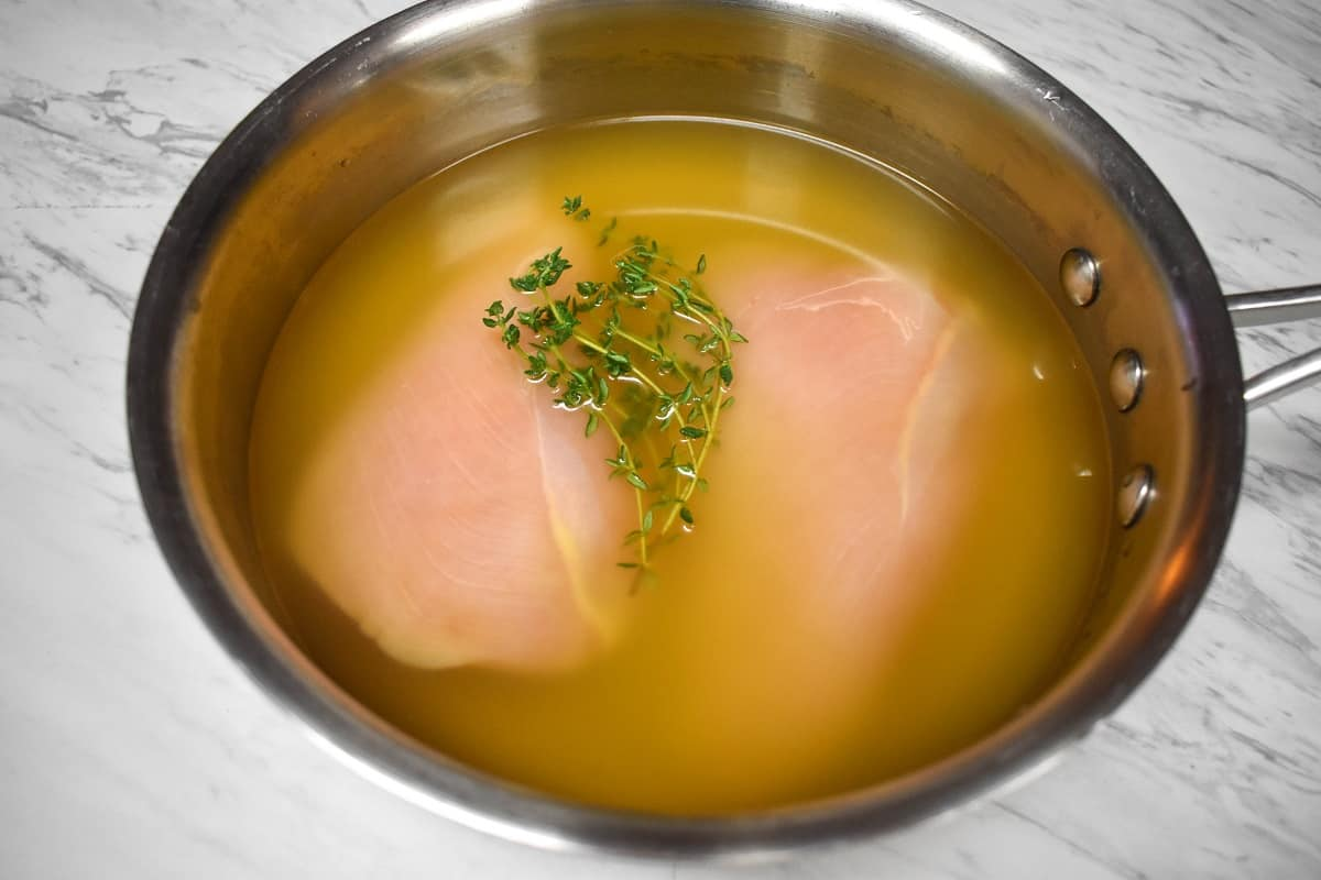 Two raw chicken breasts in a medium saucepan covered with chicken broth and thyme sprigs.