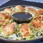 Pork potstickers arranged in a circle on a bed of lettuce on a large gray plate with a small bowl of soy sauce in the middle.