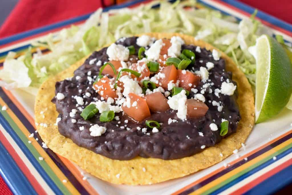 Black refried beans spread on a yellow corn tostada, topped with diced tomatoes, crumbled queso fresco and green onions. The tostada is set on shredded lettuce with a lime wedge on the side.
