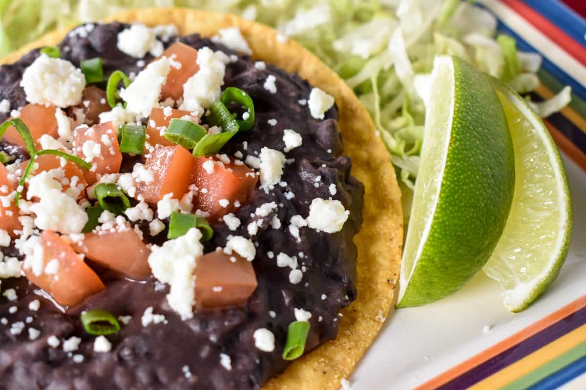 Black refried beans spread on a yellow corn tostada, topped with diced tomatoes, crumbled queso fresco and green onions. The tostada is set on shredded lettuce with two lime wedges on the side.