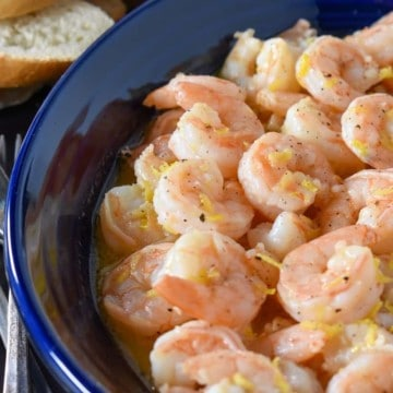 Lemon pepper shrimp served in a blue bowl with small forks on the side and toasted bread rounds in the background.