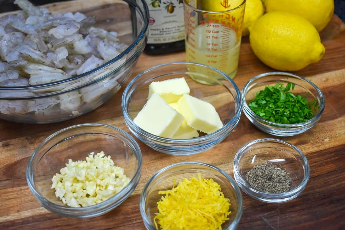 The ingredients for the lemon pepper shrimp displayed on a wood cutting board.