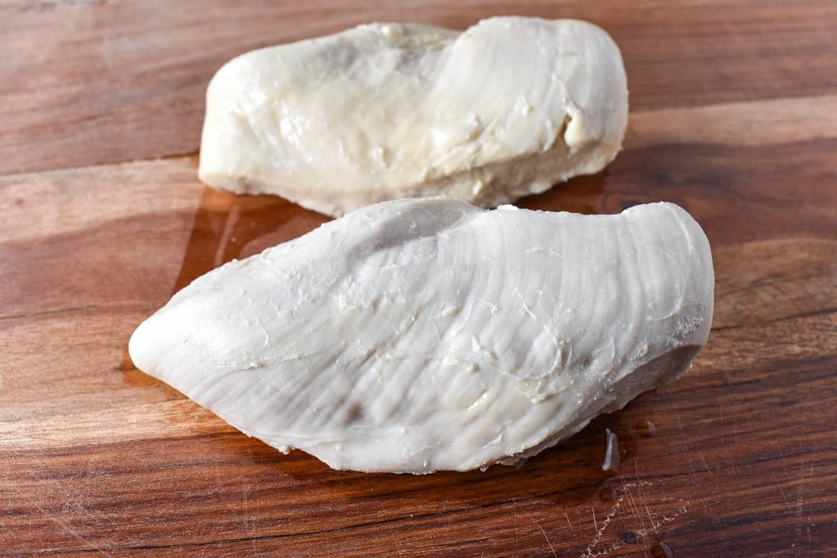 Two poached chicken breasts on a wood cutting board.