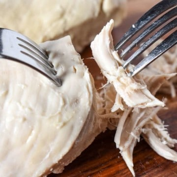 Poached chicken on a cutting board being shredded using two forks.