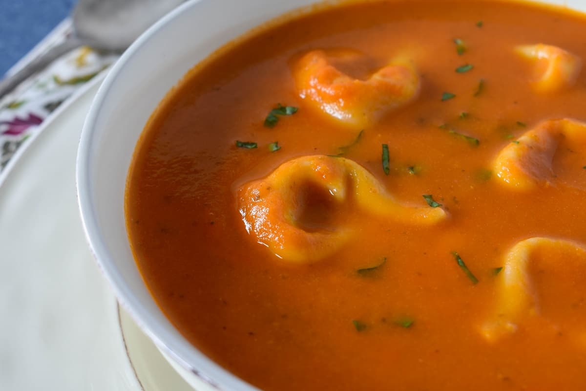 Tortellini tomato soup served in a large white bowl.
