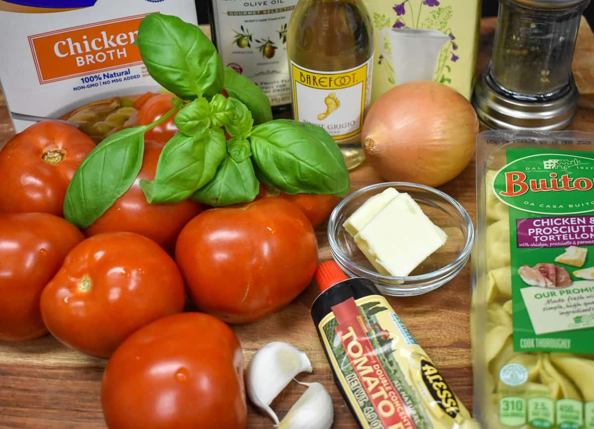 The ingredients for the tortellini tomato soup displayed on a wood cutting board.