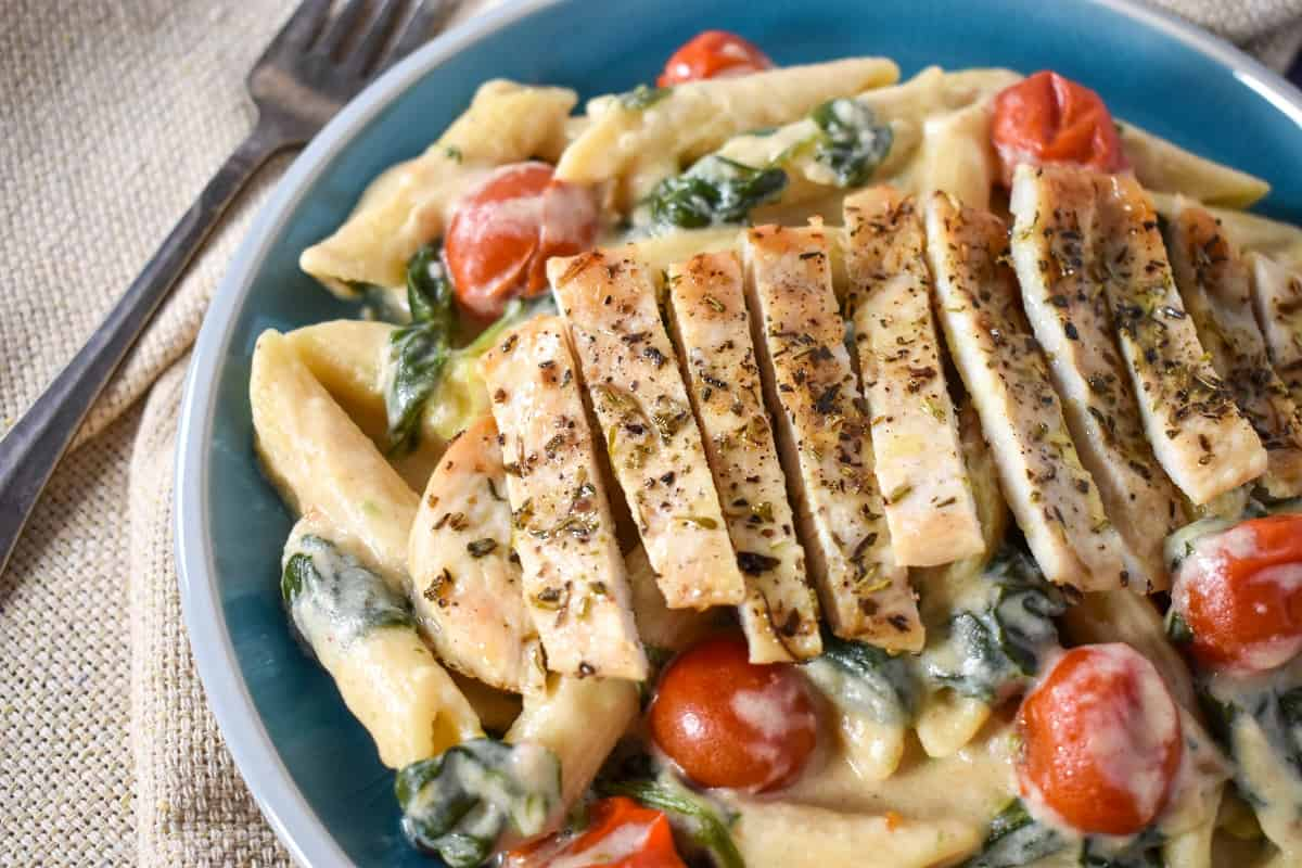 A close up image of creamy penne pasta with greens and grape tomatoes topped with sliced chicken and served in a light blue bowl.