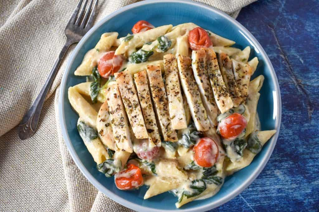 Creamy penne pasta with greens and grape tomatoes topped with sliced chicken cutlets served in a light blue plate.