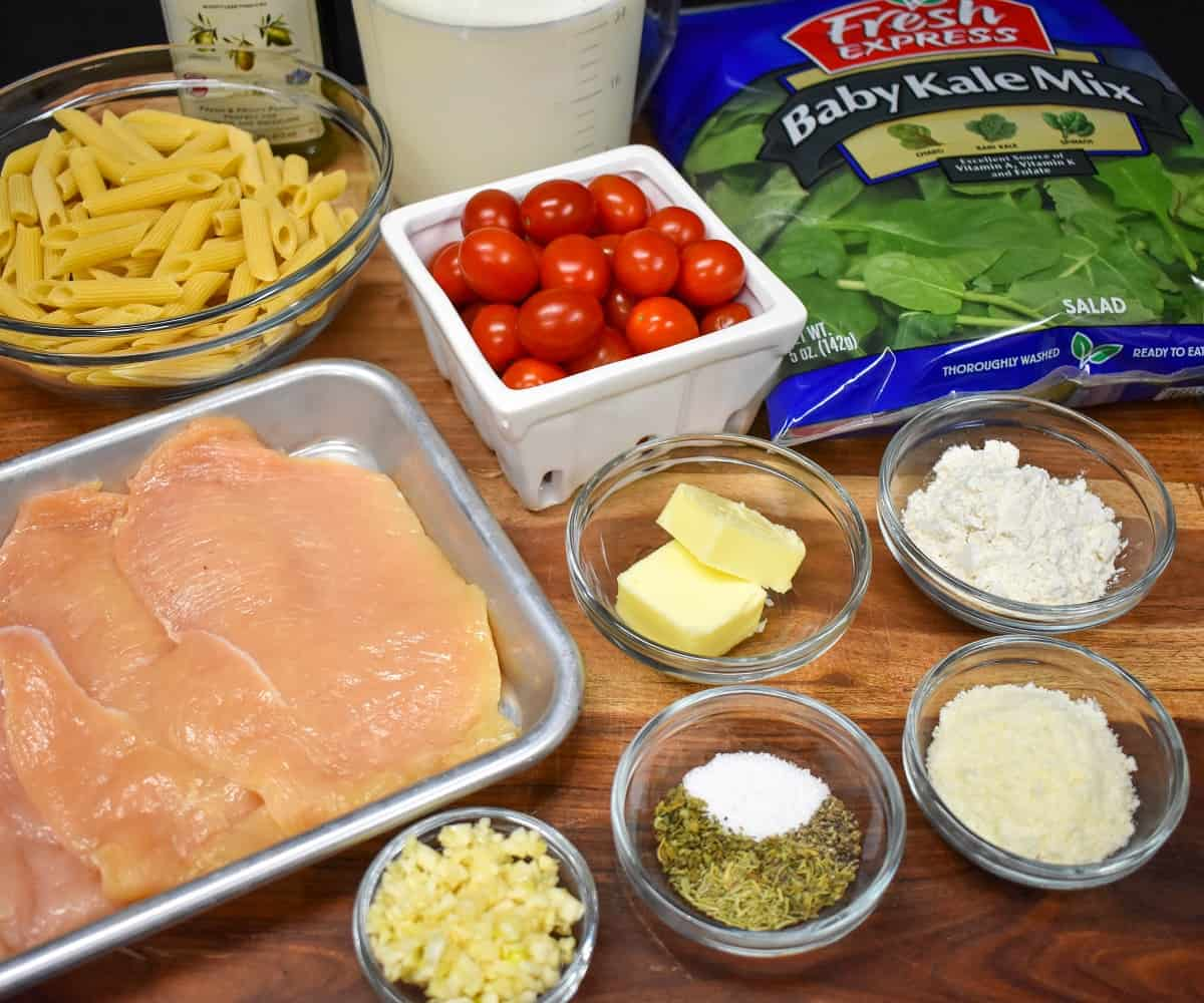 The ingredients for the creamy pasta with chicken arranged in glass bowls and displayed on a wood cutting board.