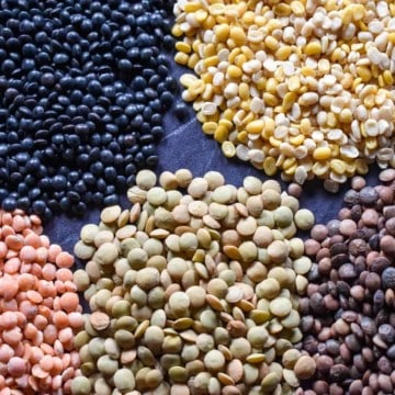 Five different varieties and color of lentils in small piles on black table.