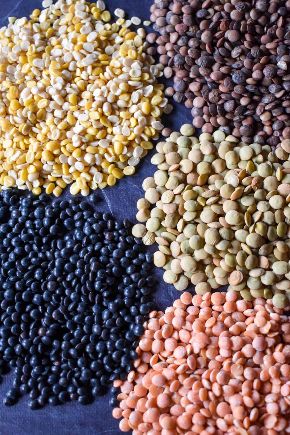 An image of the different lentils arranged in small piles on a black surface.