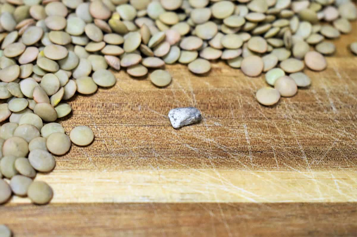 Image of dry lentils on a wood cutting board and a small stone that was found in the lentils.