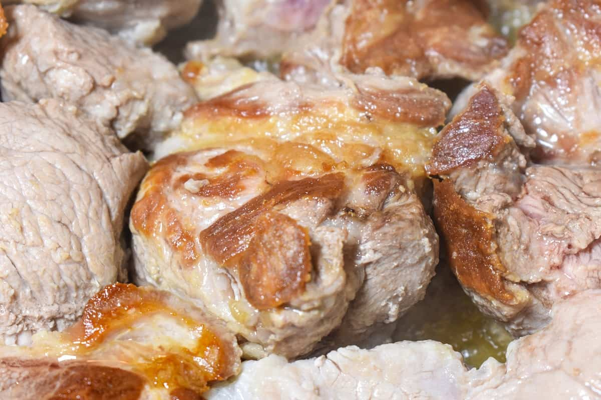 A close up image of large pork chucks browning in a pot.