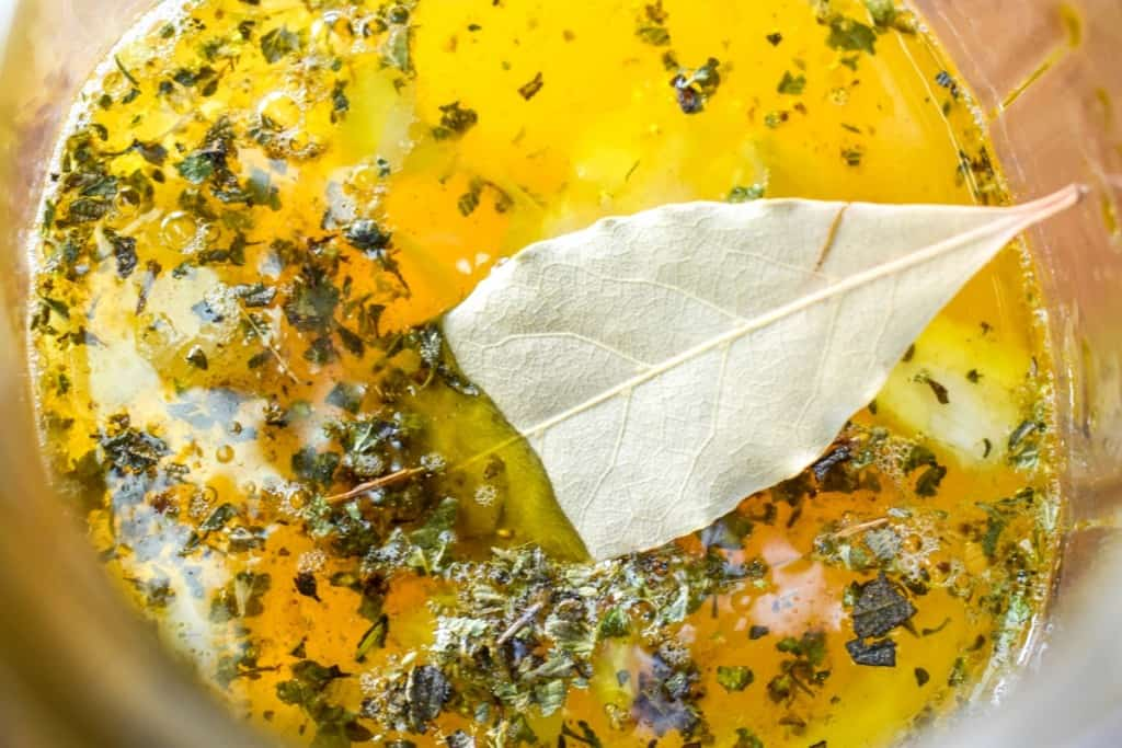 A close up image of Cuban mojo with a bay leaf half-floating on top.
