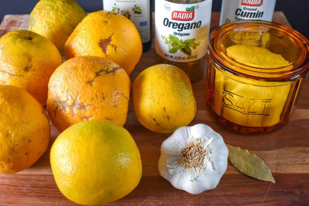 The ingredients for the mojo marinade before prepping, arranged on wood cutting board.