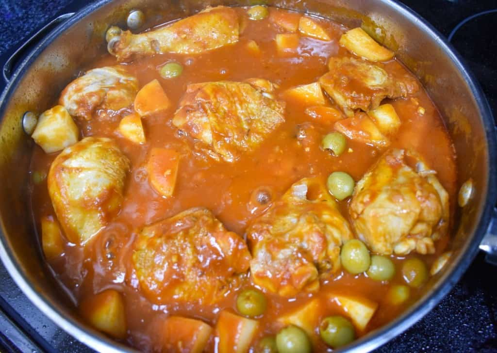 An image of the chicken, tomato sauce, potatoes and olives in a large, deep skillet.