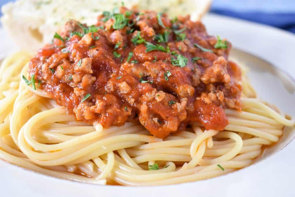 Spaghetti served on a white plate topped with sausage tomato sauce and garnished with parsley.