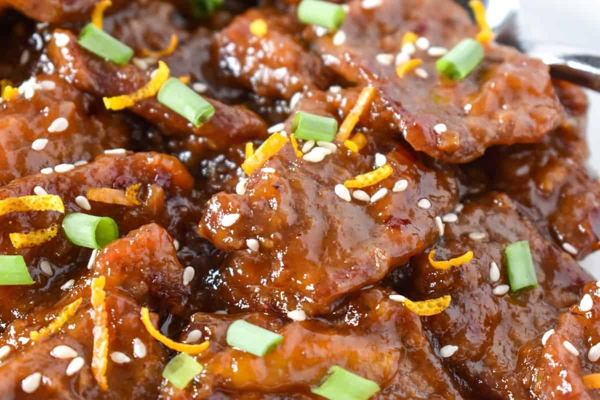 A close up image of the orange beef garnished with orange zest, sesame seeds and sliced green onions.