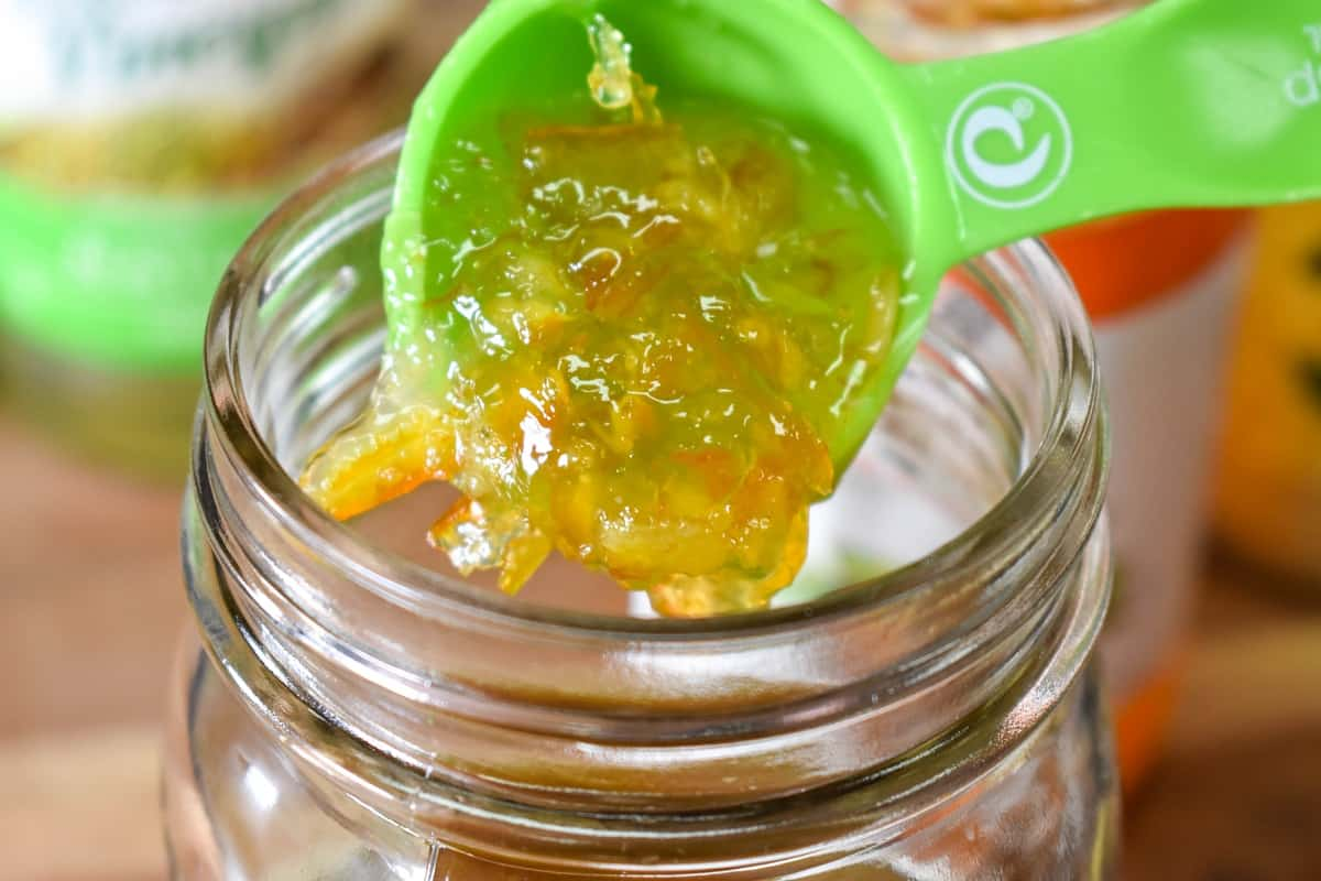 A green tablespoon adding orange marmalade to a glass canning jar.