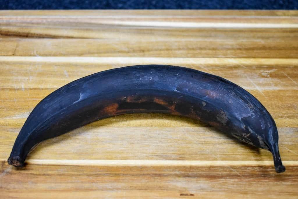 A ripe plantain on a wood cutting board.
