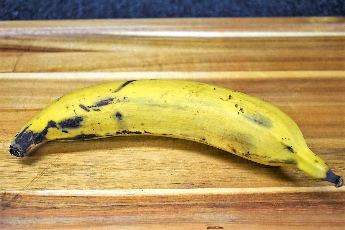 A semi-ripe plantain on a wood cutting board.