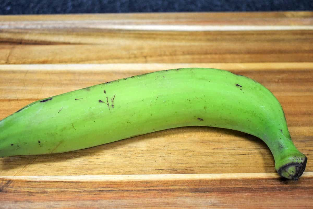 A green plantain on a wood cutting board