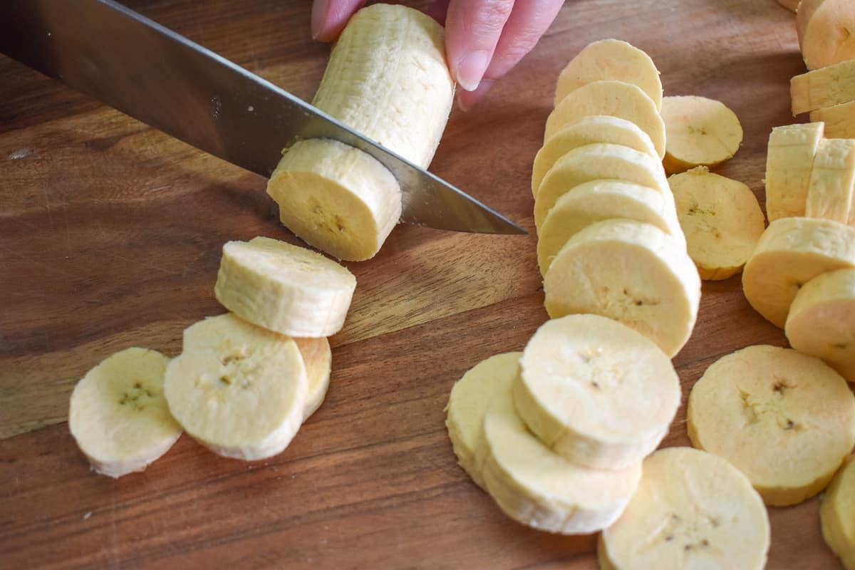 Slicing Green Plantains on a wood cutting board.