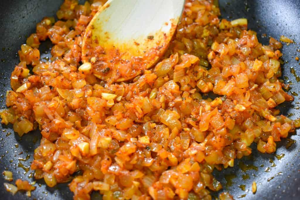 Diced onions, garlic and spices cooked with tomato paste in a black non-stick skillet with a wooden spoon in the skillet.
