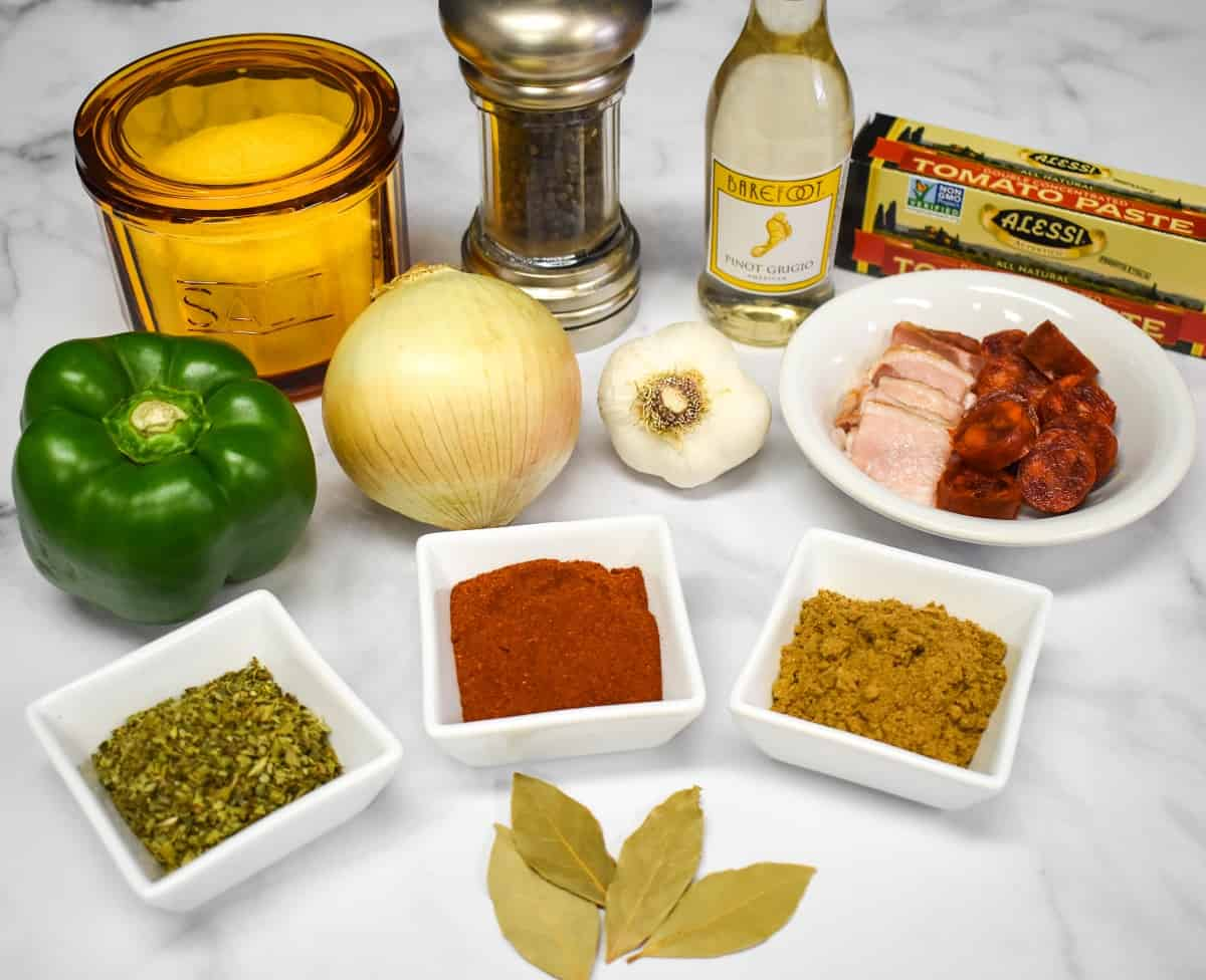 Ingredients commonly used in sofrito arranged on a white table.