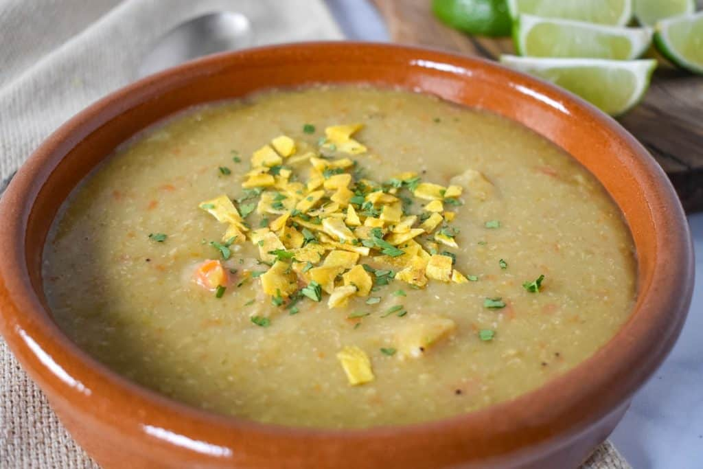 Sopa de platano served in a terracotta bowl with lime wedges in the background.