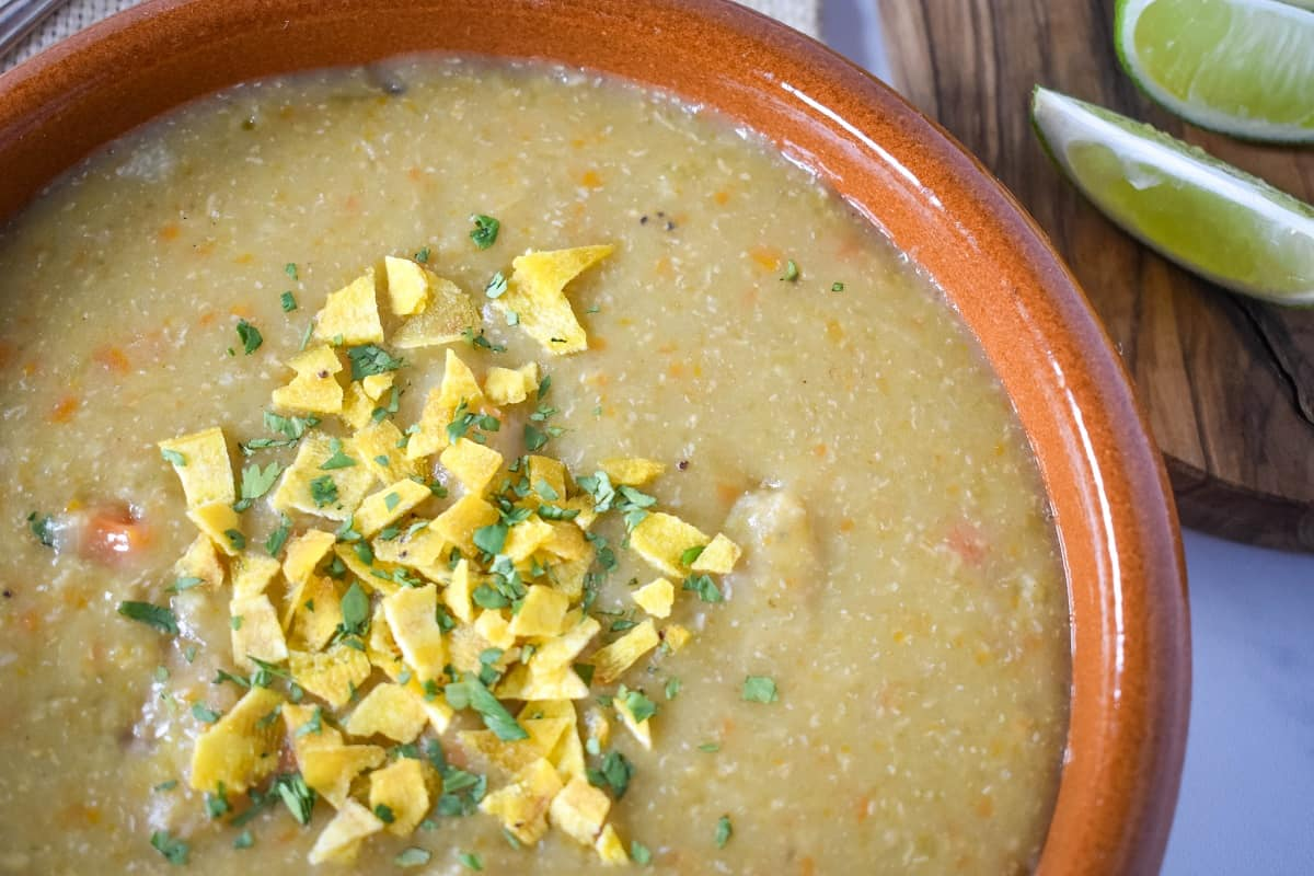Plantain soup garnished with crushed plantain chips and chopped cilantro.