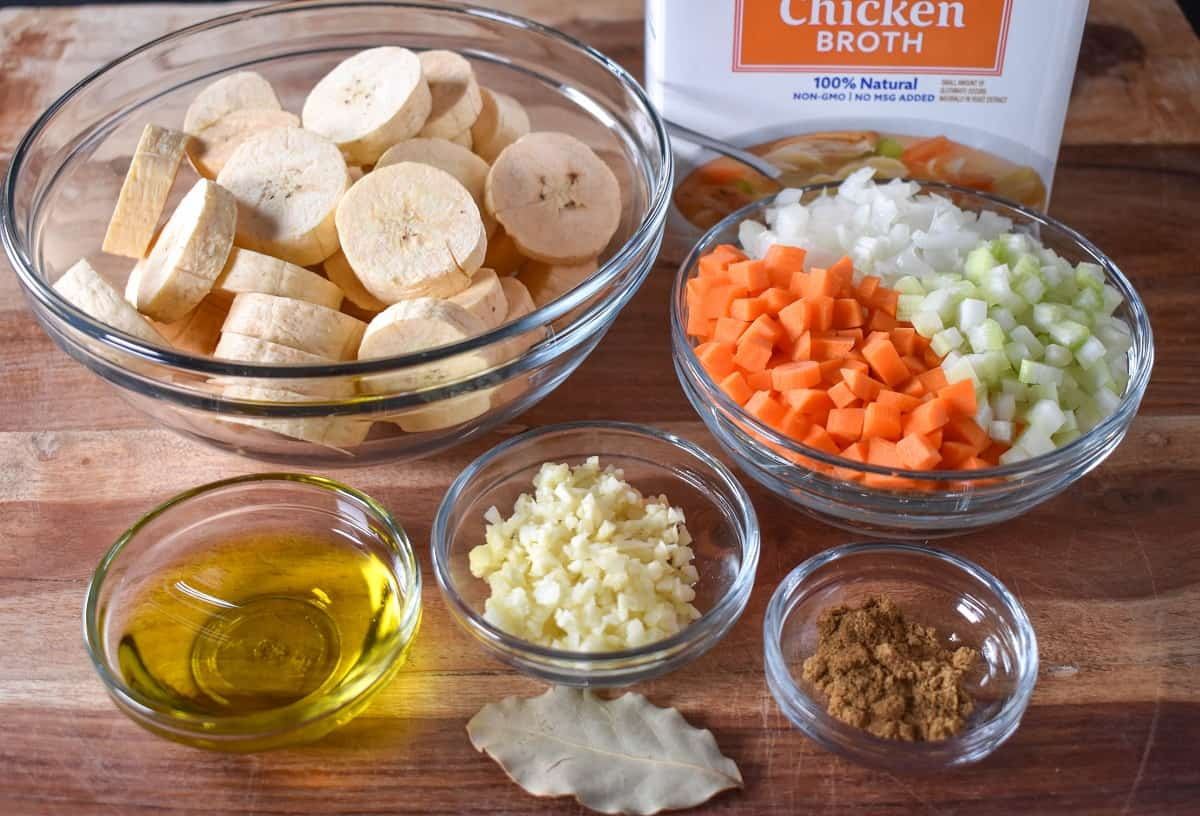 The prepped ingredients for the soup displayed in glass bowls on a wood cutting board.