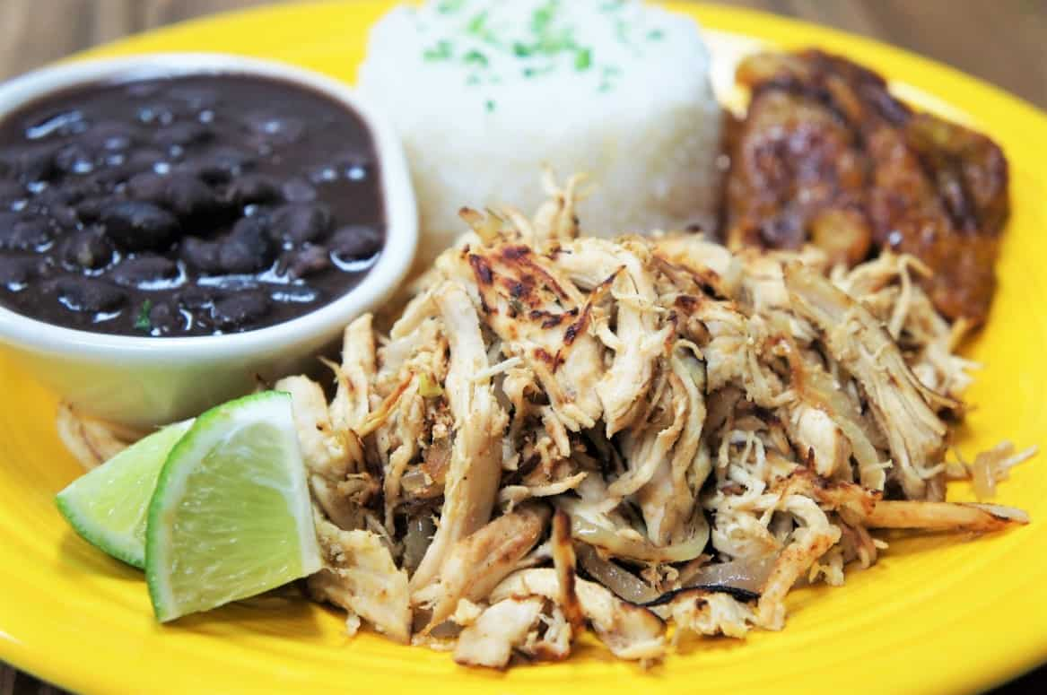 Shredded chicken served with white rice, black beans, plantains and lime wedges on a yellow plate.