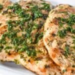 Grilled Chicken topped with chimichurri sauce served on a white platter.