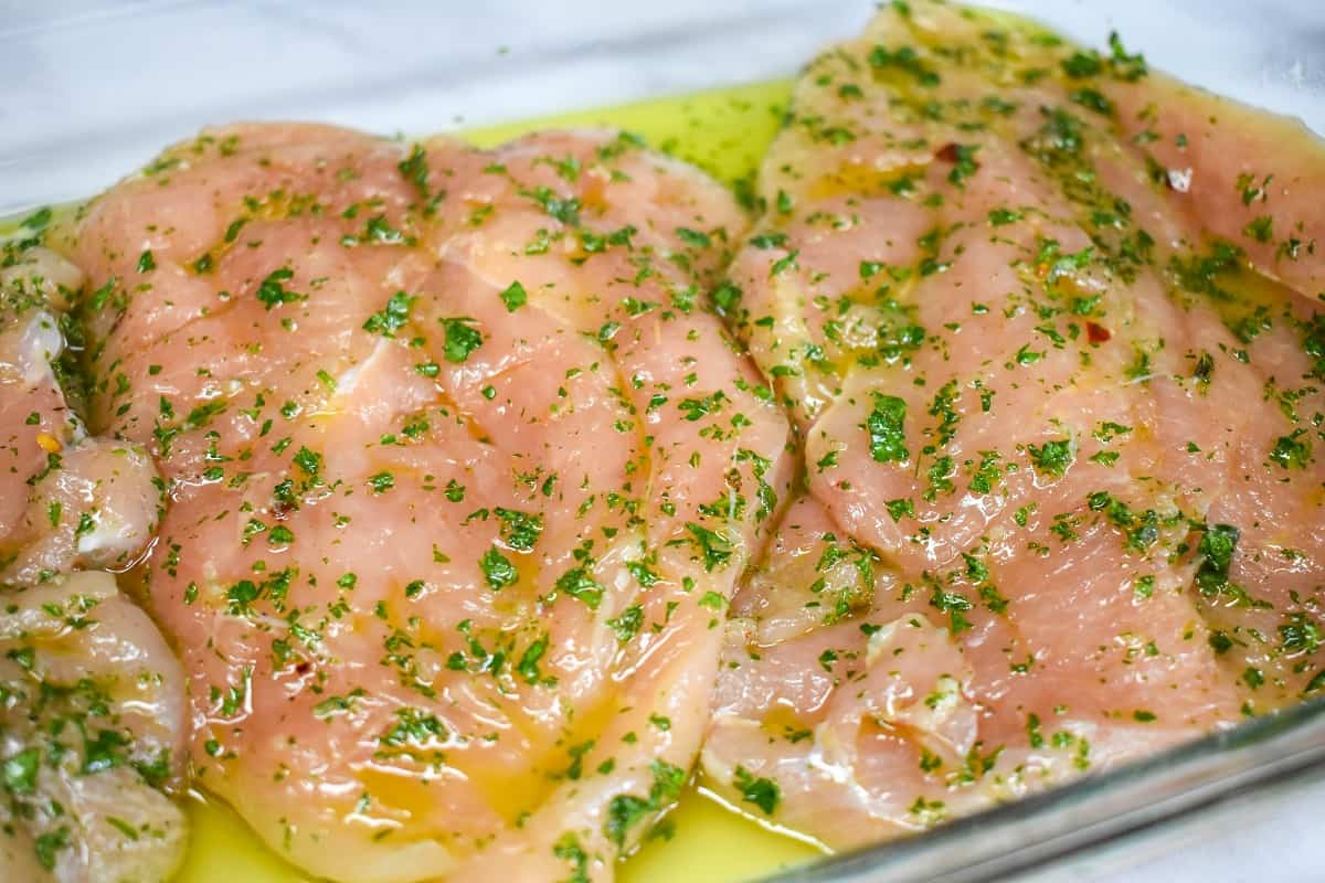 Chicken breasts marinating in chimichurri in a glass pan.