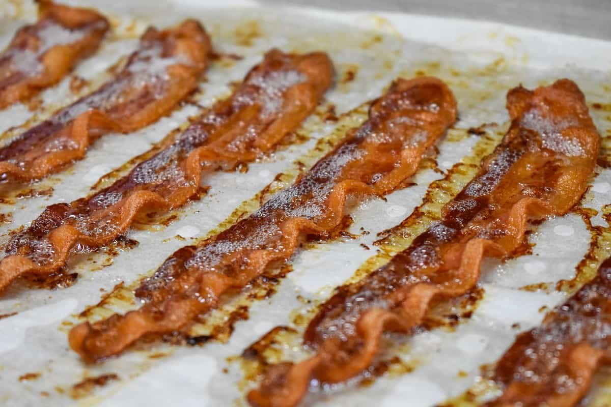Cooked, crispy bacon slices arranged on a large baking sheet that's lined with white parchment paper.