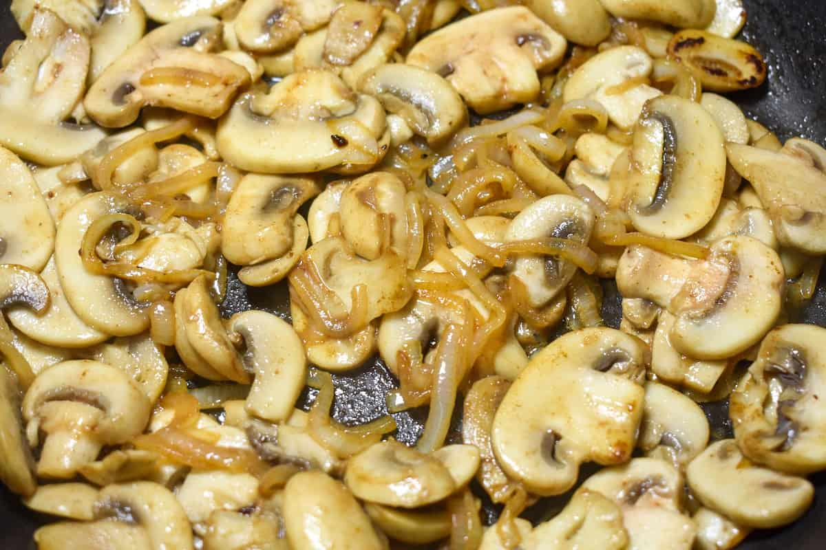 A close up of sliced onions and mushrooms cooking in a black skillet. Both the mushrooms and onions are a golden color already.