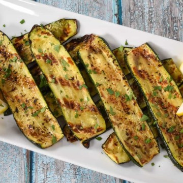 Sliced grilled zucchini arranged on a large white platter, garnished with chopped parsley and lemon wedges on the corners.