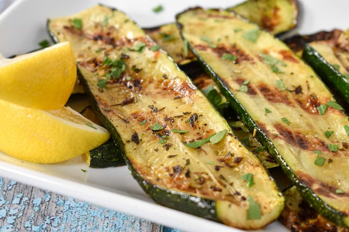 A close up image of sliced grilled zucchini arranged on a white platter, garnished with chopped parsley and lemon wedges on the corner.