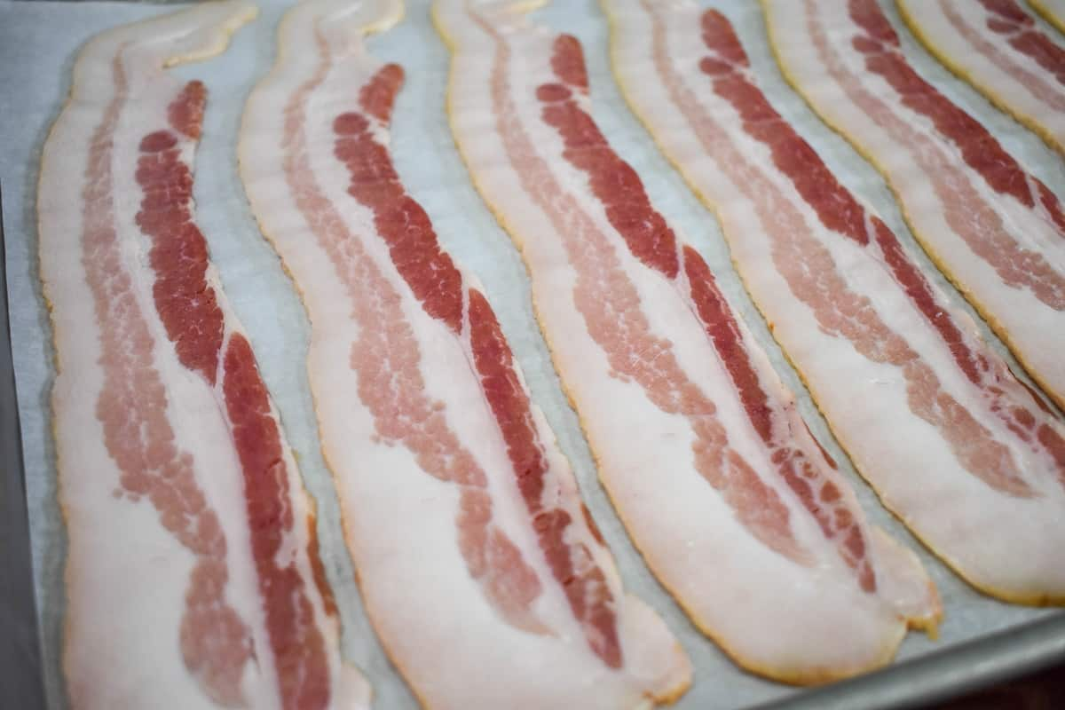 Uncooked bacon slices arranged on a large baking sheet that's lined with white parchment paper.