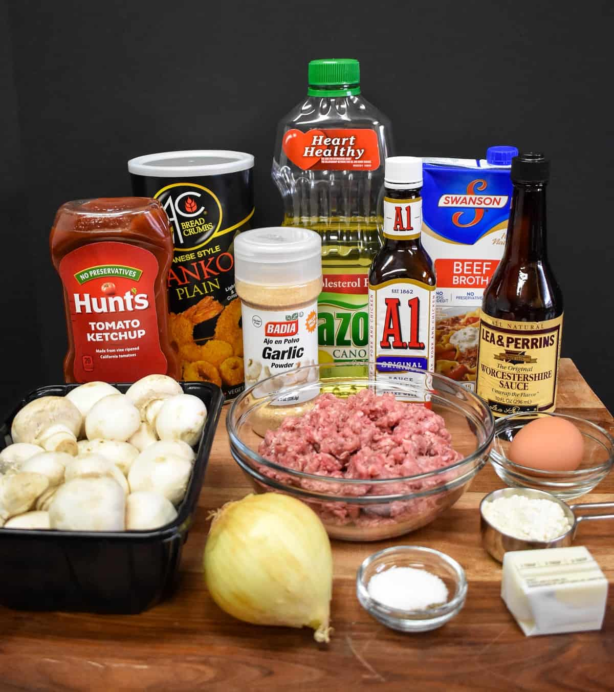 The ingredients for the Salisbury steak meatballs arranged on a large wood cutting board.
