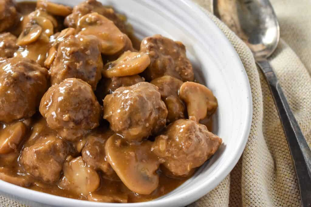 Meatballs and a mushroom gravy served in an oval white bowl on a cream colored linen with a serving spoon on the right side.